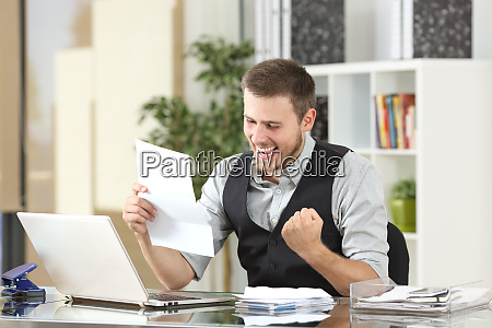 excited businessman reading a letter at