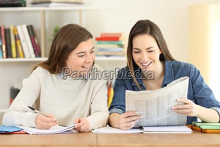 zwei glueckliche schueler lesen eine zeitung