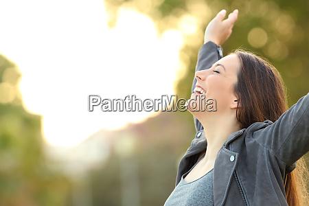 happy lady breathing fresh air raising