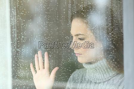 trauriges maedchen schaut durch ein fenster