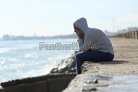 trauriges teenager maedchen allein am strand