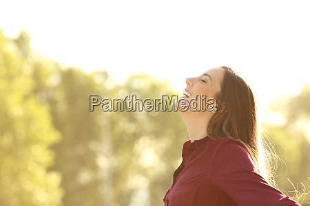 happy woman breathing fresh air outdoors