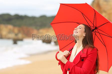 happy lady holding umbrella in winter