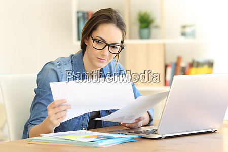 self employed working comparing documents at