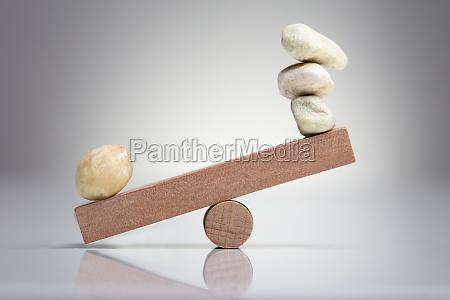 kieselsteine balancieren auf wippe