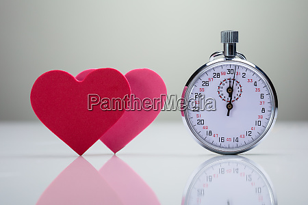 stopwatch near pink and red heart