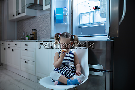 girl eating cupcake sitting in front