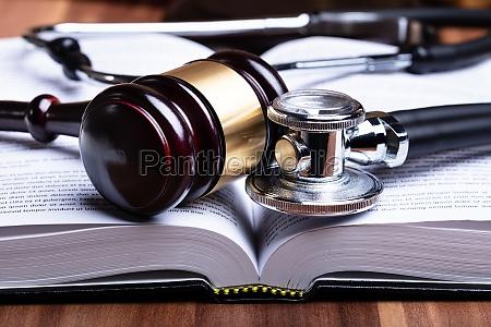 stethoskop und mallet ueber geoeffnetes gesetzbuch