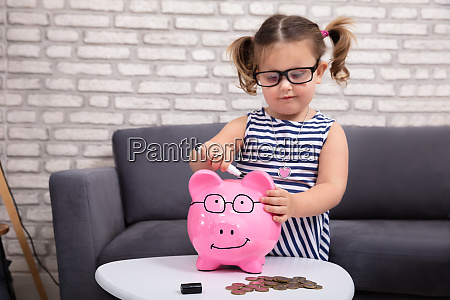 girl painting on piggy bank with