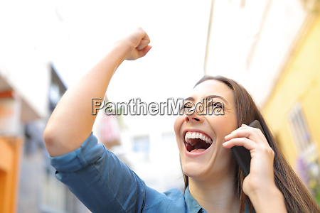 excited woman receiving good news talking