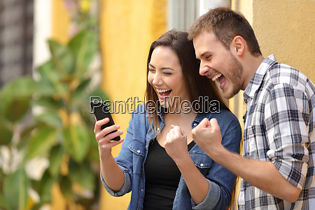 excited couple finding online offers on