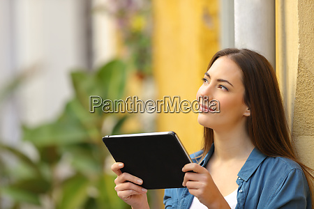 woman holding a tablet thinking looking