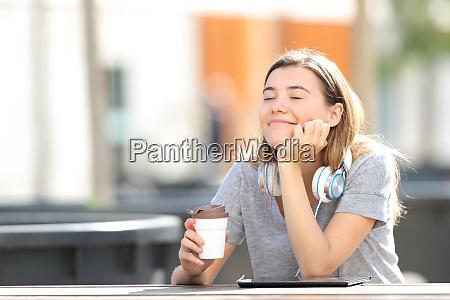 glueckliches maedchen ruht mit kaffee in