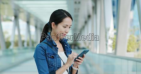 frau schaut auf smartphone im belebten