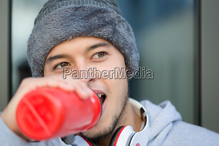 young latin man drinking water runner