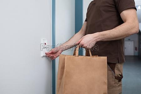 mann klingelt die tuerglocke halten papiertuete