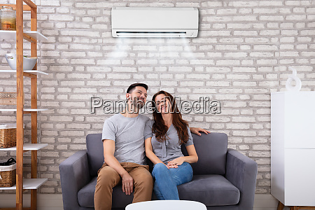 couple sitting on couch under air