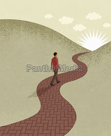 young man walking on path towards