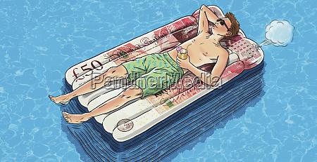 junger mann schwebt auf geld luftbett