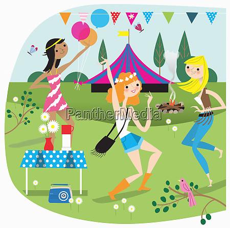 three young women having fun camping