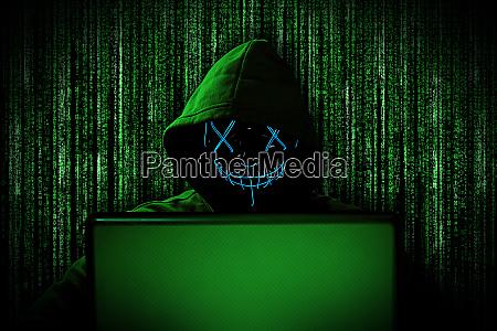 hacker mit gluehender maske hinter notebook