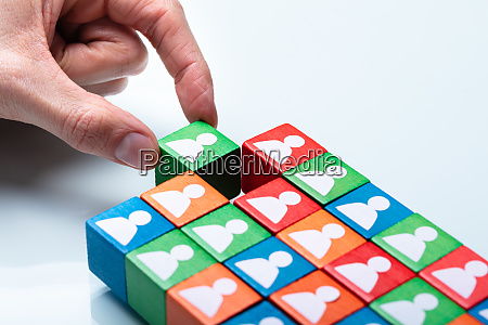 businesspersons hand holding green cubic block
