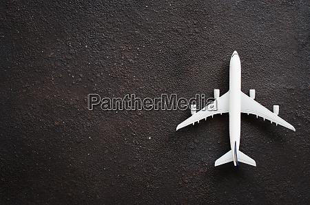 miniatur flugzeug auf dunklem hintergrund reisekonzept
