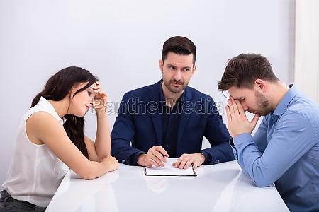 depressives paar sitzt vor richter