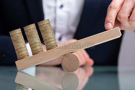 geschaeftsmann balancieren gestapelte muenzen mit finger
