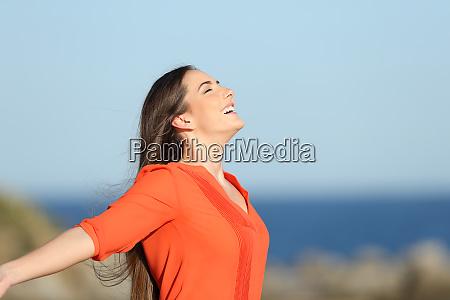 happy woman breathing fresh air in