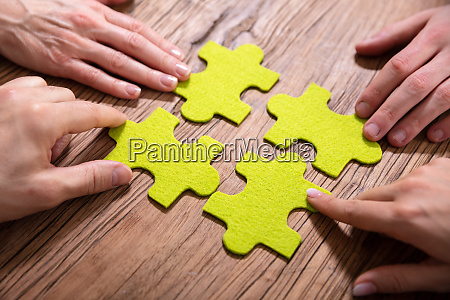 people touching jigsaw puzzle pieces