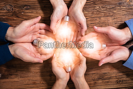 businesspeople holding light bulbs in hand