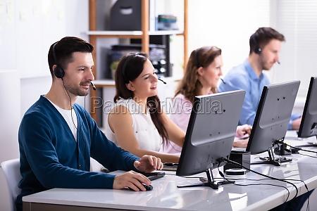 laechelnde kundendienstmitarbeiter mit kopfhoerern