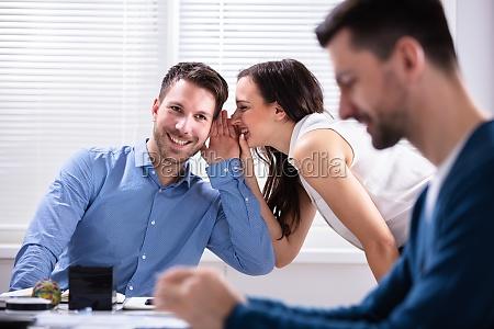 zwei geschaeftsleute die ueber ihren kollegen