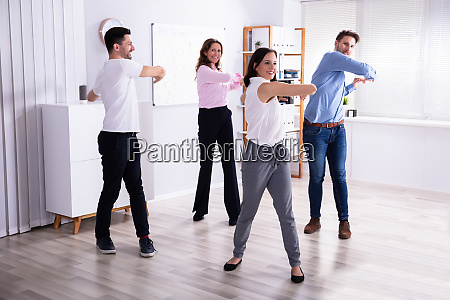 businesspeople doing stretching exercise at workplace