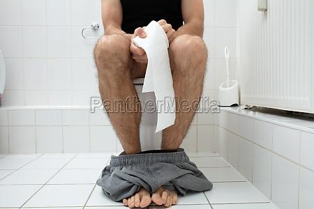 mann sitzt auf toilette schuessel halten