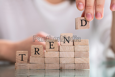hand holding wooden block from word