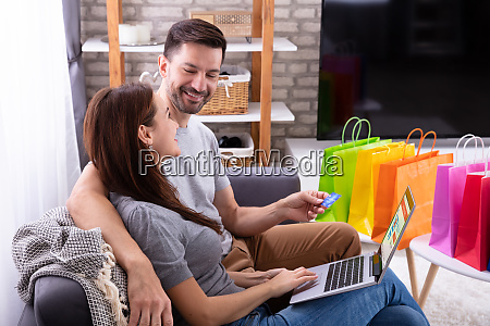 smiling couple shopping online on laptop