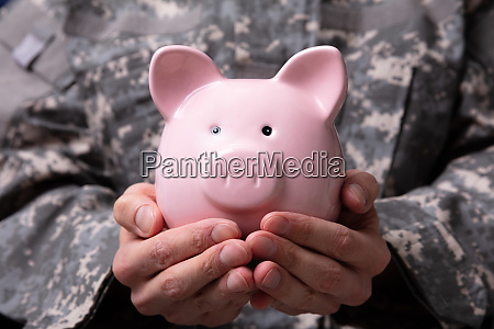 soldiers hand holding piggy bank