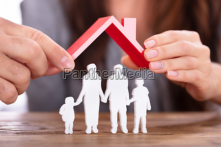 couple protecting family figures with roof