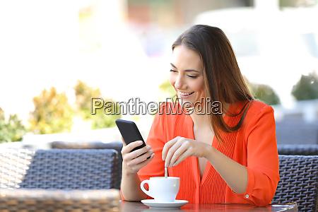 happy woman using phone stirring coffee