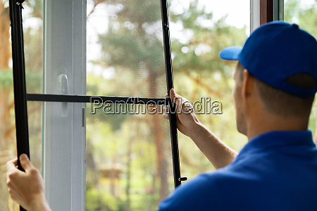 man installing insect mesh screen to