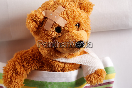 injured teddy bear with bandaged arm