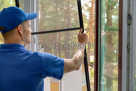 worker installing mosquito net wire mesh