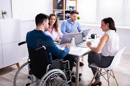 behindertenmanager sitzt mit seinen kollegen