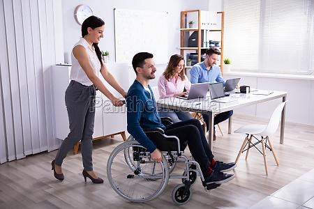 geschaeftsfrau hilft behinderten kollegen im rollstuhl