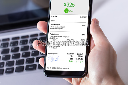 businessperson paying invoice on mobile phone