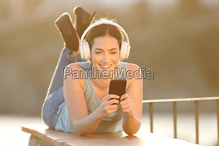 glueckliches maedchen hoert musik surfen telefon