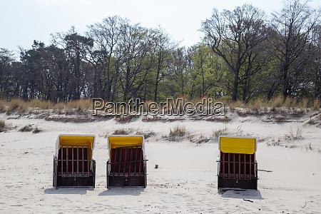 drei einsame strandkoerbe am strand von