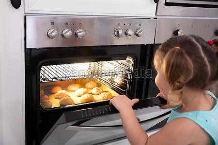 maedchen backen cookies im ofen